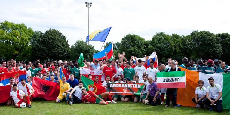 Ein große Gruppe Fußballspieler mit verschiedenen Länderflaggen