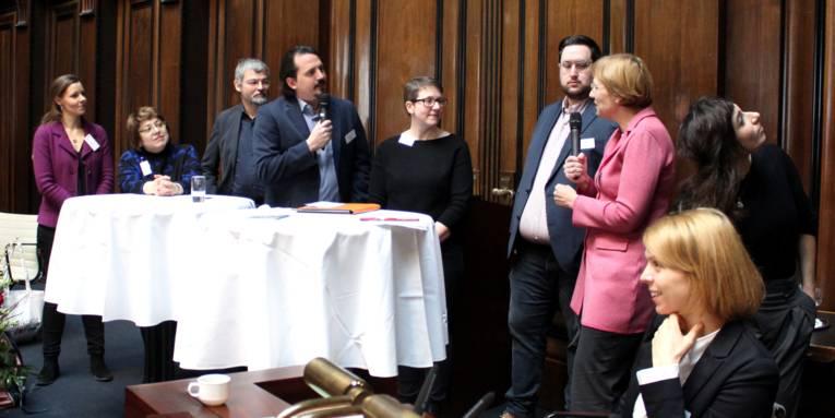 Acht Personen - fünf Frauen und drei Männer - stehen im Hodlersaal des Neuen Rathauses hinter Stehtischen. Ein Mann und eine Frau halten Mikrofone in der Hand und blicken zueinander. Rechts daneben sitzt eine weitere Frau.