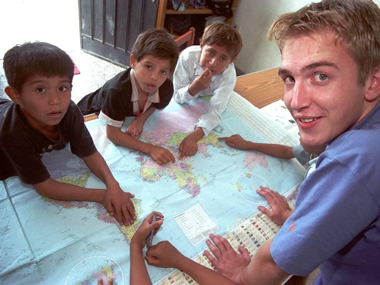 Ein junger Erwachsener und einige Kinder beugen sich über eine Weltkarte und schauen in die Kamera