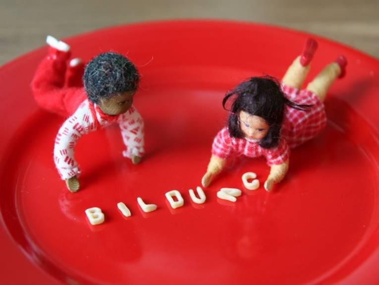 Bildungshungrig: zwei Puppen mit Buchstabennudeln auf einem Teller