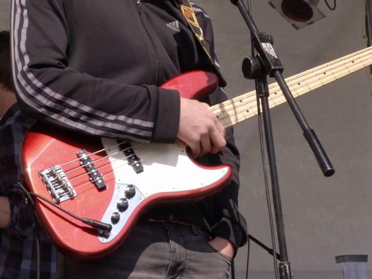 Der Bildausschnitt zeigt einen Jugendlichen, der einen Bass in den Händen hält