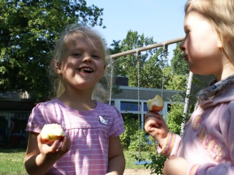 Zwei Mädchen essen selbstgepflückte Äpfel