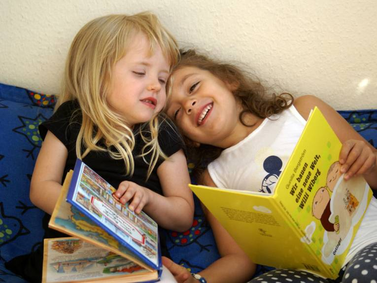 Zwei Mädchen albern mit ihren Bilderbüchern herum