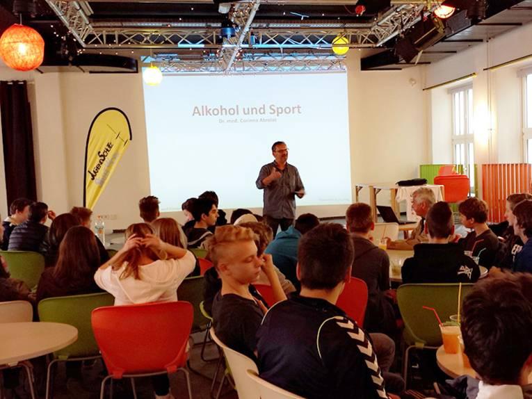 Redner des Jugendschutzes vor Teilnehmern des Workshops zum Thema Alkohol und Sport