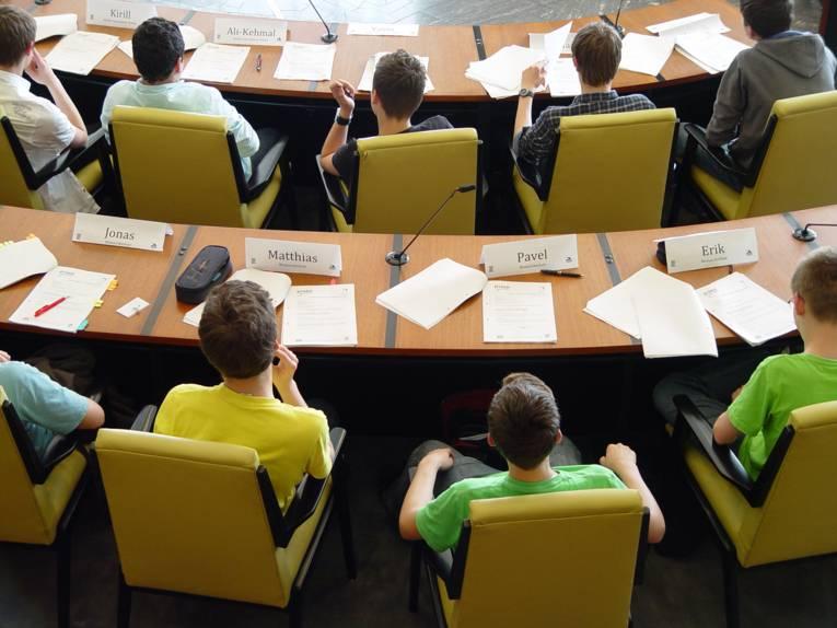 Blick von oben auf einige Jugendliche, die im Ratssaal der Landeshauptstadt Hannover sitzen. Vor den Jugendlichen liegen verschiedene Dokumente auf den Tischen.