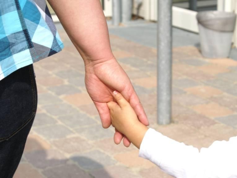 Ein kleines Mädchen geht an der Hand einer erwachsenen Frau. man sieht nur die beiden Arme und Hände.