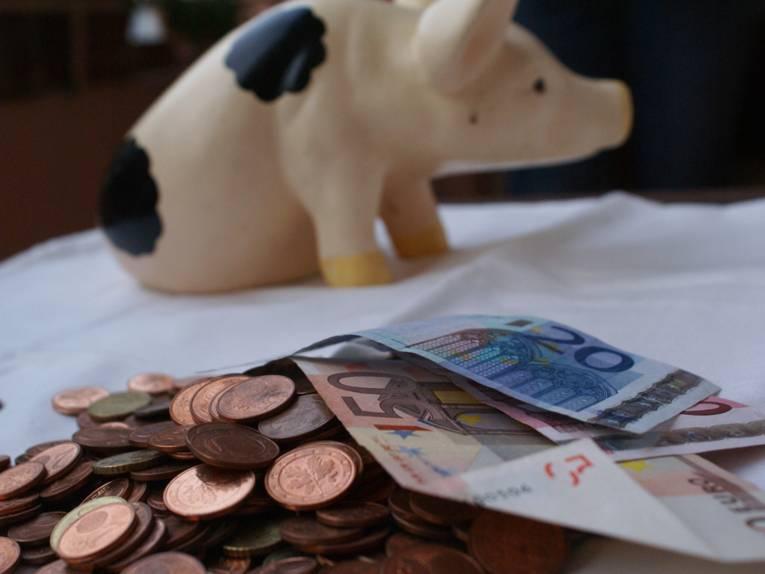 Kleingeld, Geldscheine und im Hintergrund ein Sparschwein