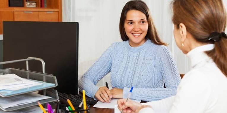 Beratungssituation in einem Büro, bei der sich zwei Frauen mit Stift und Zettel an einem Schreibtisch besprechen.
