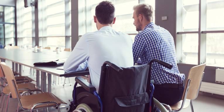 Zwei junge Männer sitzen nebeneinander an einem Besprechungstisch und unterhalten sich; einer davon mit Rollstuhl.