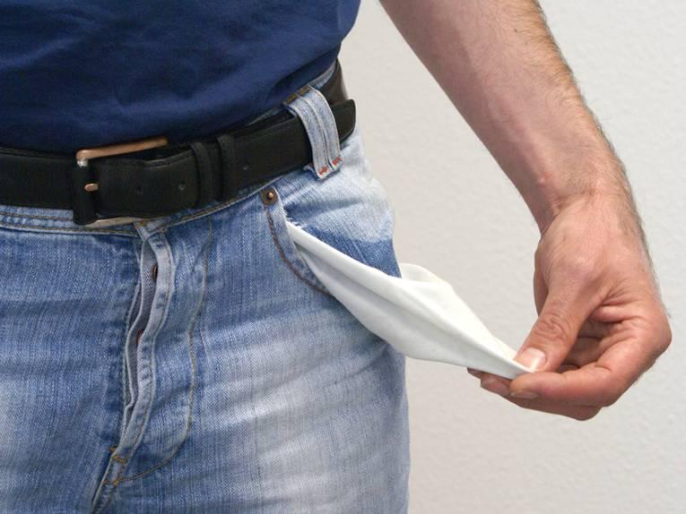 Eine Person zeigt eine leere Hosentasche