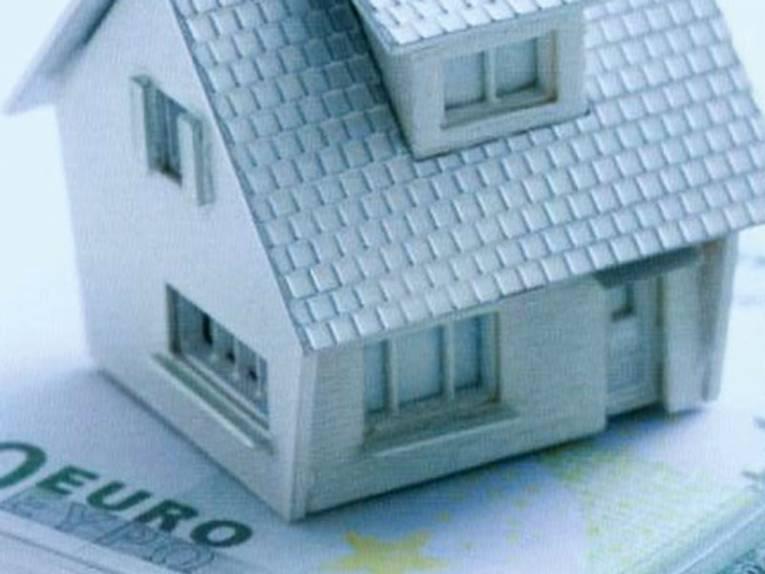 Ein Hausmodell steht auf einem Euro-Geldschein