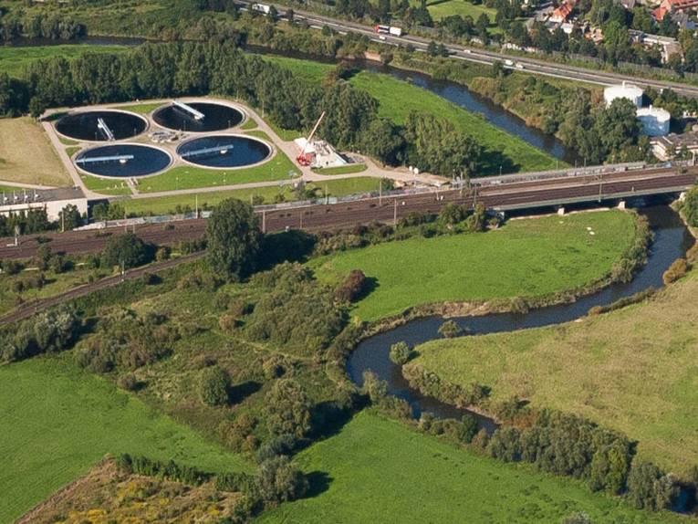Luftaufnahme von vier Behandlungsbecken einer Kläranlage mit dem Fluß Leine, der sich daneben entlangschlängelt