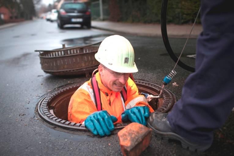 Kanalarbeiter beim Einstieg in einen Kanal