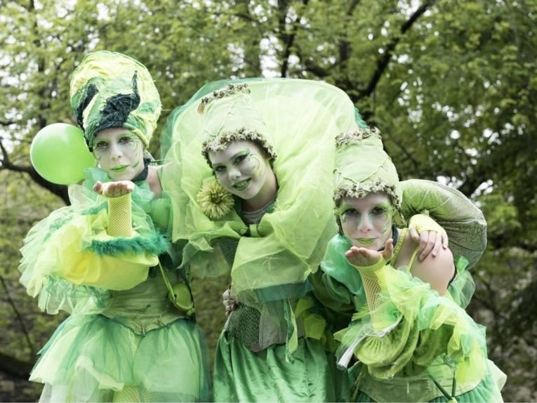 Drei grün gekleidete Fantasiefiguren (Walk-Acts) beim Autofreien Sonntag