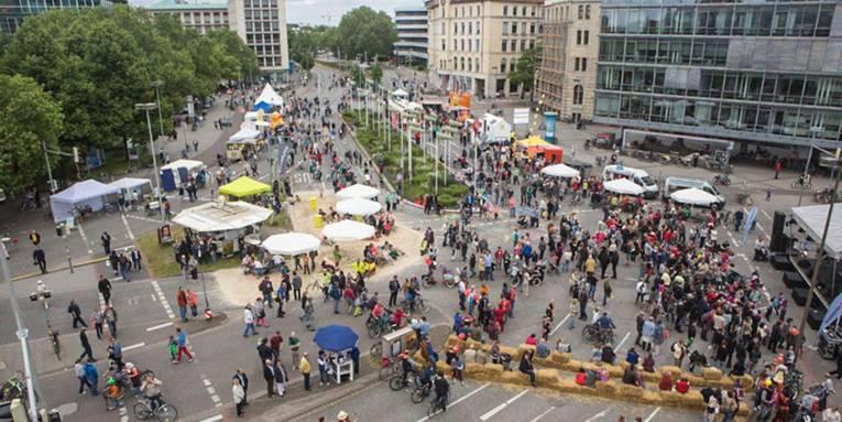 Fußgänger und Fahrradfahrer, Informationsstände und Heuballen, die zum Sitzen einladen, auf dem Aegidientorplatz