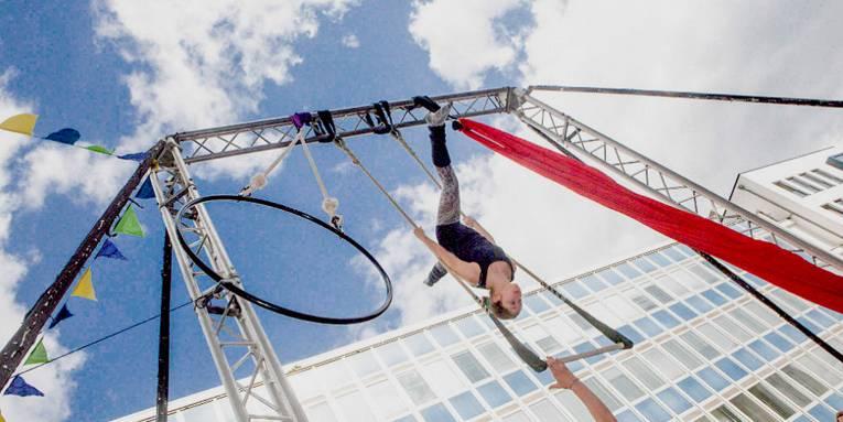 Eine junge Frau vollführt kopfüber eine artistische Darbietung an einem hoch aufgehängten Trapez vor blauem Himmel