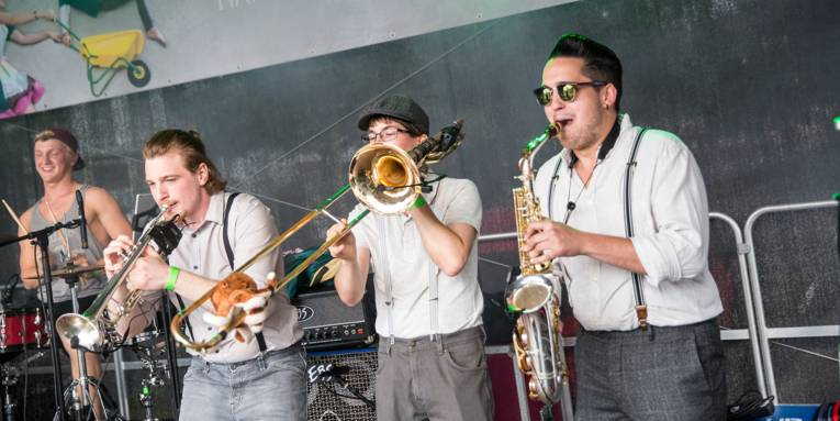 Drei Blechbläser und ein Schlagzeuger auf einer Bühne beim Autofreien Sonntag