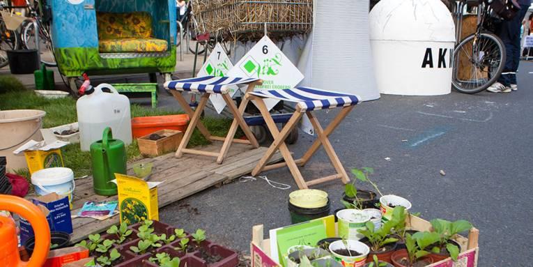 Artikel, die man zum Selberziehen von Gemüse benötigt, neben einem mit Stroh gefüllten Einkaufswagen