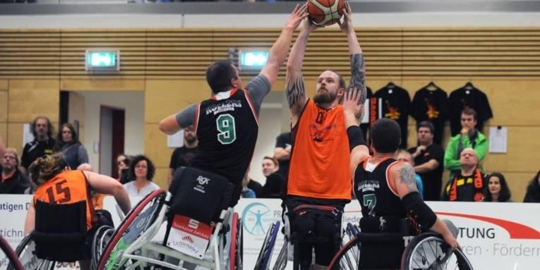 Beim Rollstuhlbasketball kämpfen vier Spieler um den Ball.