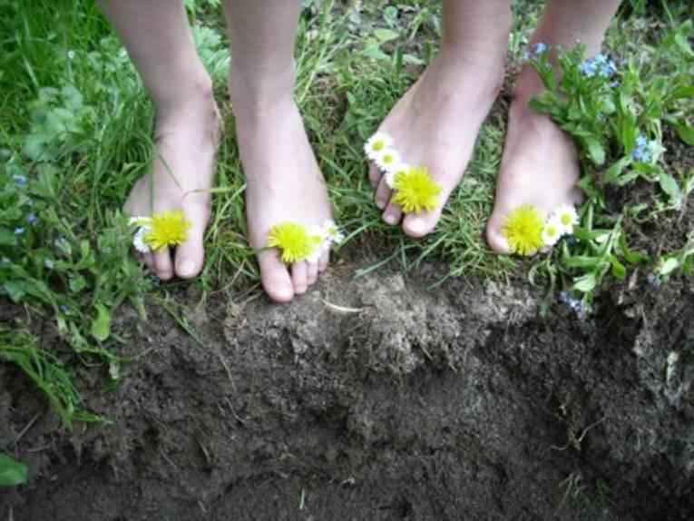 Blüten von Löwenzahn und Gänseblümchen schmücken Füße, die auf Gras und schwarzer Erde stehen.