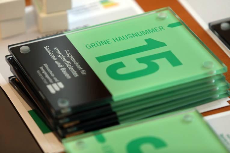 "Schilder der ""Grünen Hausnummer"" gestapelt"