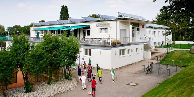 Fußballnachwuchs vor Clubgaststätte mit Solardach