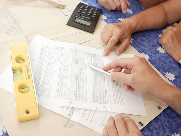 Nahaufnahme eines Antragsformulars mit Taschenrechner auf einem Tisch, an dem mehrere Personen sitzen