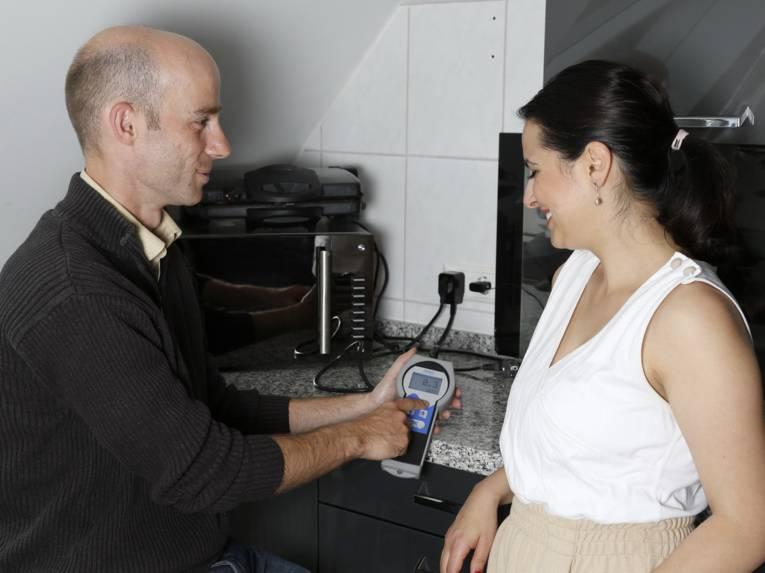 Ein Techniker mit einem Strommessgerät, neben ihm eine Frau