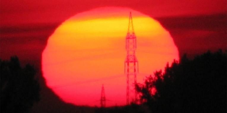 Die Sonne geht auf und erleuchtet einen Strommasten