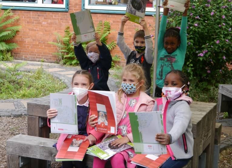 Kinder halten Schulhefte aus Recyclingpapier hoch.