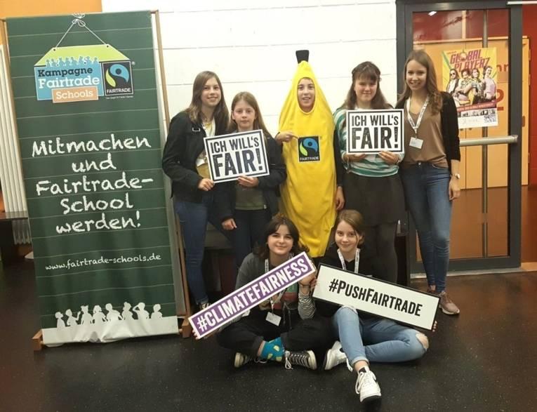 Schüler*innen mit Schildern zum Fairen Handel und in einem Bananenkostüm. Daneben ein Aufsteller zur Fairtrade Schools Kampagne.