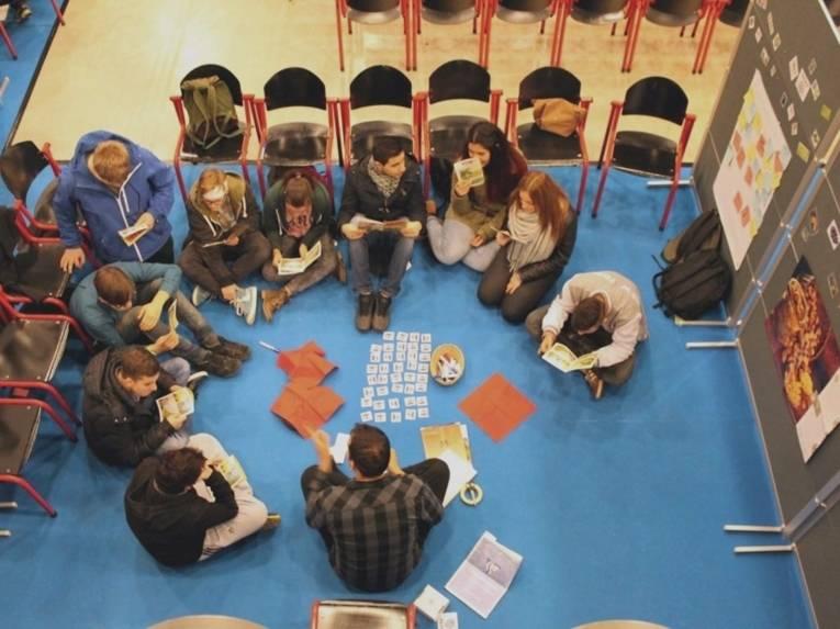 Schülerinnen und Schüler sitzen im Kreis auf den Boden neben Stellwänden und arbeiten mit Karten