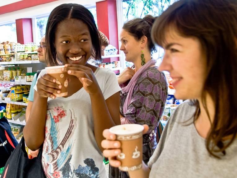 Zwei junge Frauen in einem Geschäft trinken fair gehandelten Kaffee