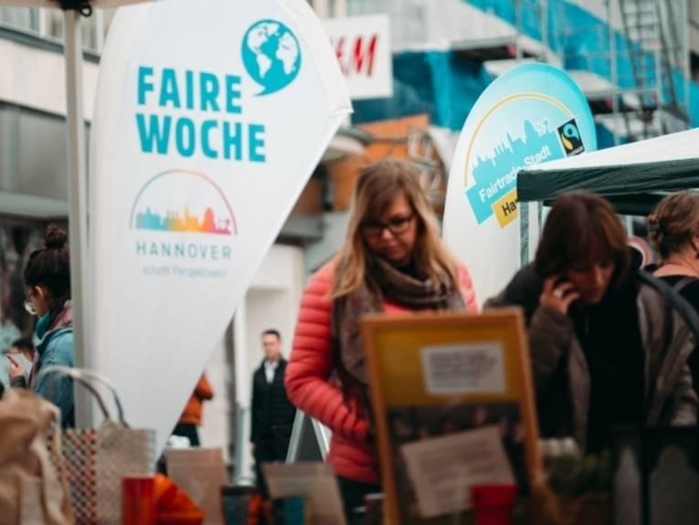 """Infostand mit Beachflag """"Faire Woche"""" und Besucherin."""