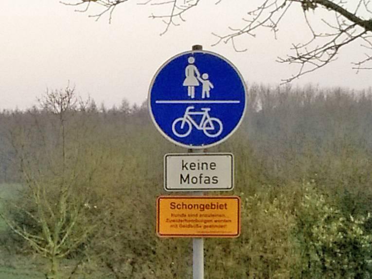 Schild vor einer großen Wiese.