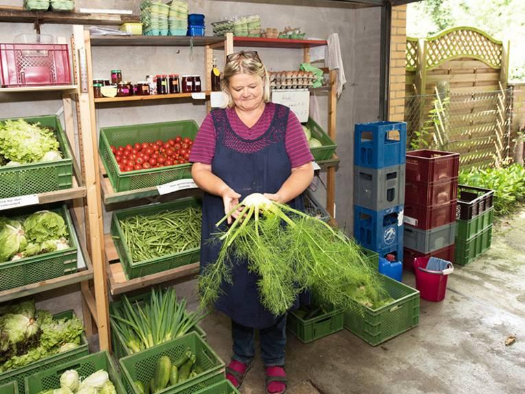 Frau mit Gemüse in einem Hofladen.