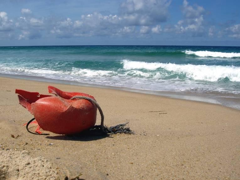 Angespülter oranger Plastikmüll an einem Strand
