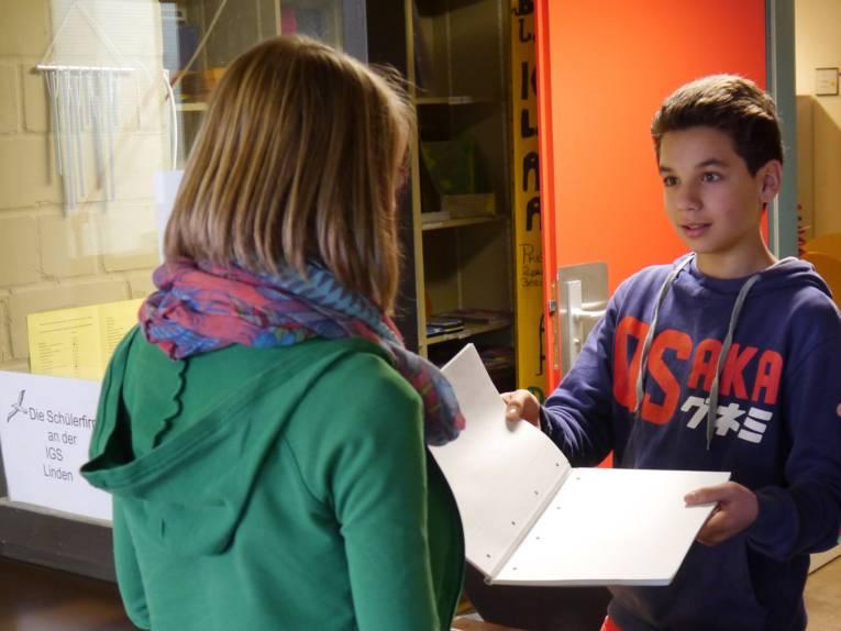 Ein Junge präsentiert einem Mädchen an einer Art Durchreiche ein Schulheft