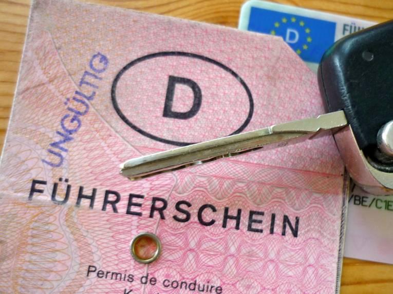 """Ein alter rosafarbene Führerschein ist mit einem """"Ungültig""""-Stempel versehen, darauf liegt ein Fahrzeugschlüssel; im Hintergrund ist ein Fragment eines neues Führerscheins zu sehen."""