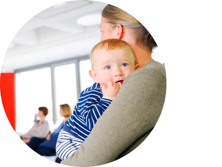 Eine Frau hält ein Baby auf dem Arm, im Hintergrund sitzen Personen.