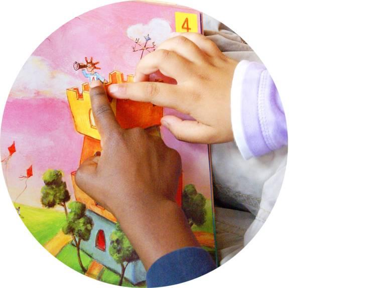 Zwei Kinderhände zeigen auf ein Bild in einem Buch.