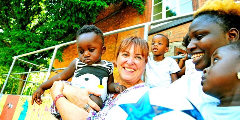 Zwei Erwachsene und vier Kinder vor einem Backsteinhaus.