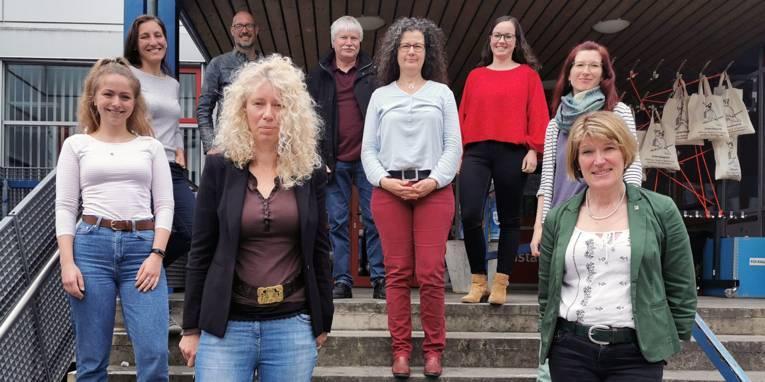 Eine Personengruppe posiert auf einer Treppe.