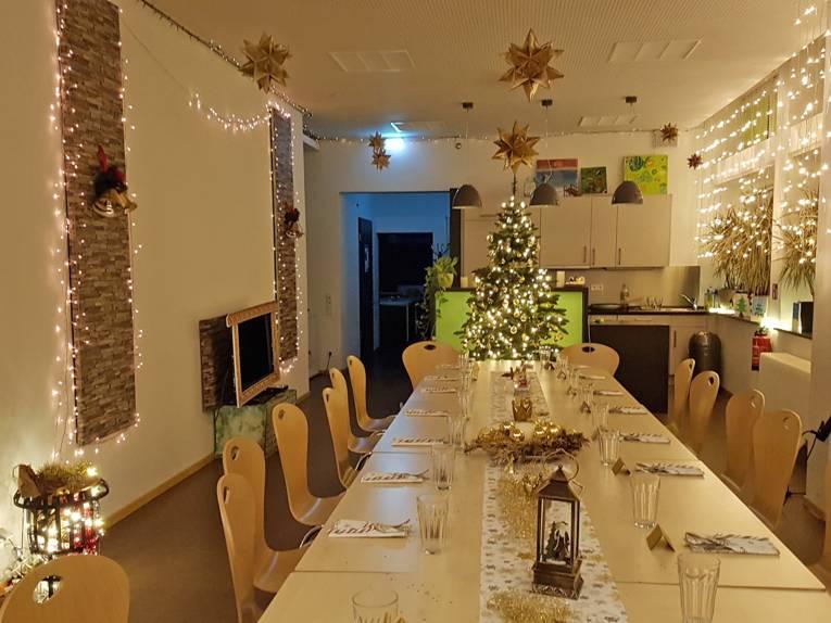 Ein langgestreckter Raum mit einem festlich eingedeckten Tisch und gemütlicher Beleuchtung im Jugendtreff Marienwerder.