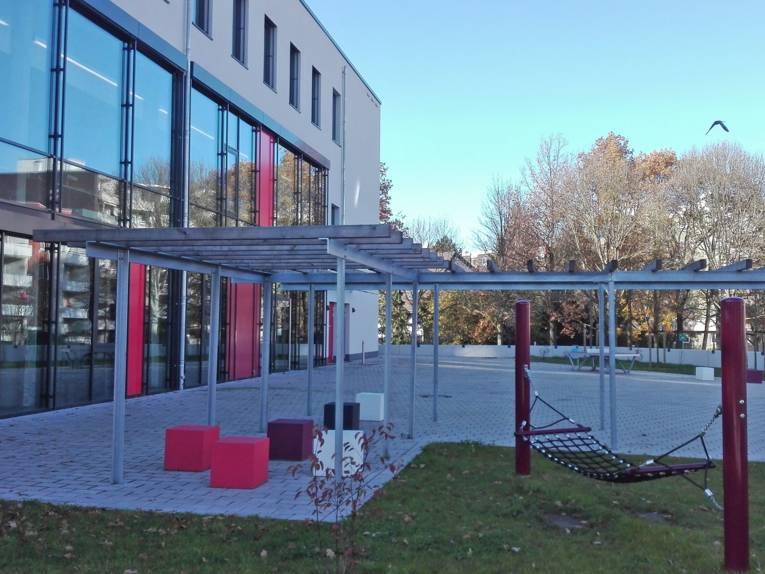 Außenansicht des Jugendzentrums Mühlenberg mit Außenbereich (Hängematte, Tischtennisplatte)