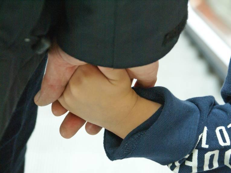 Kinderhand wird von einer Erwachsenenhand gehalten