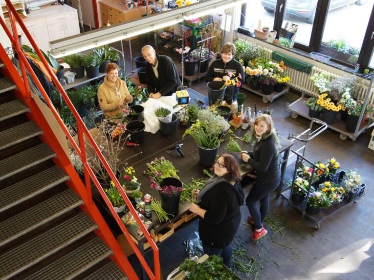 Eine Gruppe beim Erstellen von Blumengebinden.