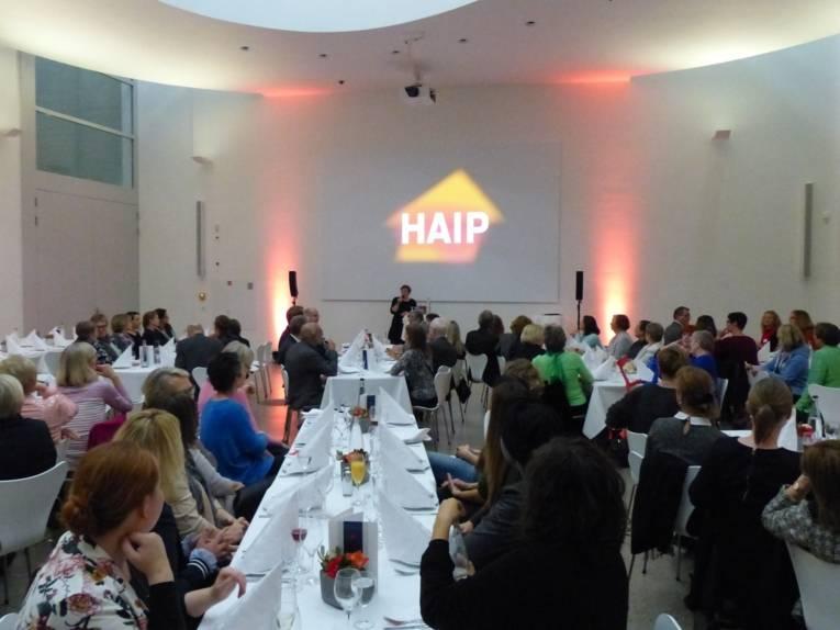 Die Gleichstellungsbeauftragte der Landeshaupstadt Hannover, Friederike Kämpfe, steht an der Stirnseite eines festlich geschmückten Raumes und begrüßt die an Tischen sitzenden Gäste.