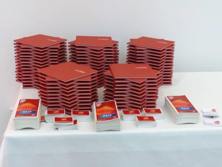 Die roten Jubiläumsbroschüren sowie Flyer von HAIP liegen zum Mitnehmen bereit.