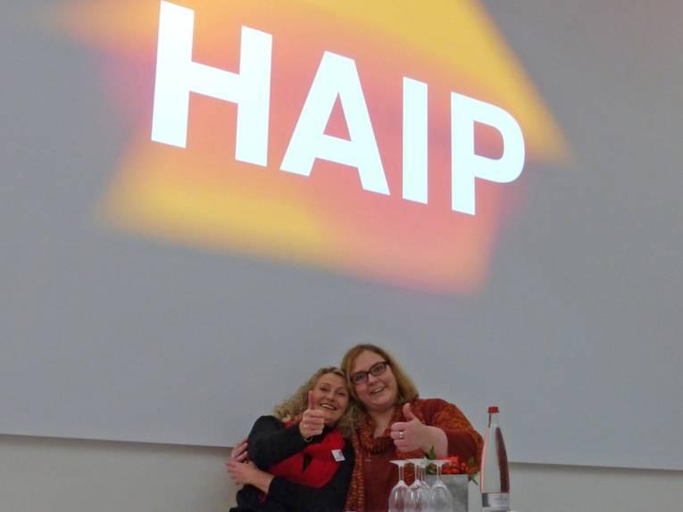 Zwei Frauen zeigen unter dem HAIP-Logo mit dem Daumen nach oben